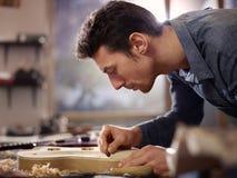 Italiensk hantverkare som fungerar i lutemakerseminarium Royaltyfri Bild