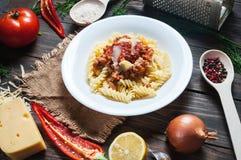 Italiensk köttsåspasta och nya läckra ingredienser för att laga mat på lantlig bakgrund Fotografering för Bildbyråer