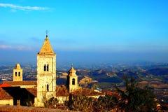 Italiensk katolsk kyrka med härligt bergigt landskap i bakgrunden arkivbild