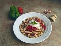 Italiensk kokkonst - kornpasta med söt peppar och tomatsås royaltyfria bilder