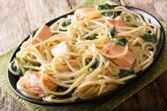 Italiensk kokkonst: spagetti med laxen, gräddost och spenat Royaltyfri Foto