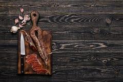 Italiensk korvkorv, kniv och vitlök Royaltyfri Bild