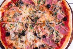 Italiensk läcker varm pizza på träplattan, på den vita tabellen Arkivbild