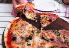 Italiensk läcker varm pizza på träplattan, på den vita tabellen Arkivfoto