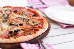 Italiensk läcker varm pizza på träplattan, på den vita tabellen Fotografering för Bildbyråer