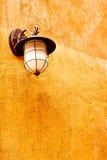 Italiensk lampa på den orange väggen Fotografering för Bildbyråer