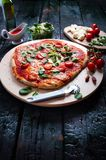 Italiensk mat, kokkonst Margherita pizza på en svart, trätabellen med igredients gillar tomater, sallad, ost, mozzarellaen, basil arkivfoton