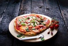 Italiensk mat, kokkonst Margherita pizza på en svart, trätabellen med igredients gillar tomater, sallad, ost, mozzarellaen, basil arkivbilder