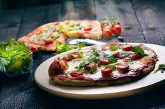 Italiensk mat, kokkonst Margherita pizza på en svart, trätabellen med igredients gillar tomater, sallad, ost, mozzarellaen, basil fotografering för bildbyråer