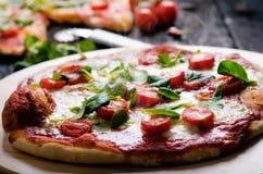 Italiensk mat, kokkonst Margherita pizza på en svart, trätabellen med igredients gillar tomater, sallad, ost, mozzarellaen, basil arkivfoto