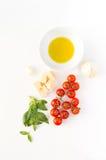 Italiensk mat med röda tomater, pasta, basilika spricker ut, ost, garl Arkivbild