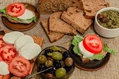 Italiensk mat - mozzarella, tomater, oliv, olivgrön deg och bröd Royaltyfria Bilder