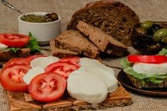 Italiensk mat - mozzarella, tomater, oliv, olivgrön deg och bröd Arkivfoton