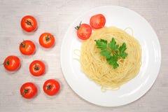 Italiensk mat: pasta på en stor vit platta bredvid de röda körsbärsröda tomaterna och de gröna oliven Arkivbilder