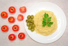 Italiensk mat: pasta på en stor vit platta bredvid de röda körsbärsröda tomaterna och de gröna oliven Royaltyfri Foto