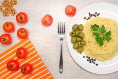 Italiensk mat: pasta på en stor vit platta bredvid de röda körsbärsröda tomaterna och de gröna oliven Royaltyfri Bild