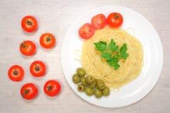 Italiensk mat: pasta på en stor vit platta bredvid de röda körsbärsröda tomaterna och de gröna oliven Fotografering för Bildbyråer