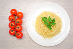 Italiensk mat: pasta på en stor vit platta bredvid de röda körsbärsröda tomaterna och de gröna oliven Royaltyfri Fotografi