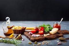Italiensk matbakgrund med basilika, spagetti, parmesan, olivolja, vitlökingredienser på stentabellen kopiera avstånd royaltyfria bilder