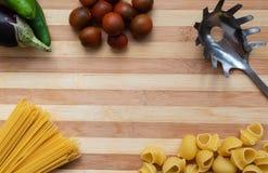 Italiensk matbakgrund med grönsaker och pasta arkivbild