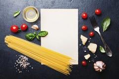 Italiensk matbakgrund med okokt spagetti, tomat, basilika, ost, vitlök och olivolja eller matlagningpasta på bästa sikt för tabel royaltyfria foton