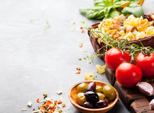 Italiensk matbakgrund med vinrankatomater, basilika, spagetti, olivingredienser på utrymme för stentabellkopia Arkivbild