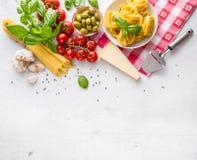 Italiensk matkokkonst och ingredienser på vitbetongtabellen Ost för parmesan för tomater för olivolja för spagettitagliatelleoliv arkivbilder