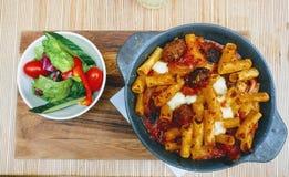 Italiensk maträtt för pasta och för sallad Arkivfoto