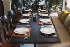 Italiensk matställetabell för åtta med bestick, plattor, exponeringsglas, servetter och naperies på tabellen arkivbild