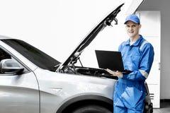 Italiensk mekaniker med den brutna bilen och bärbara datorn royaltyfria foton