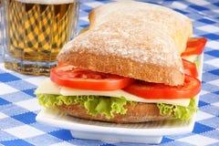 Italiensk paninosmörgås och öl Arkivfoto