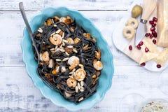 Italiensk pasta är svart med musslor och räkor Parmesan skaldjur, olika mellanmål för matställe Ljus disk och vit bakgrund fotografering för bildbyråer
