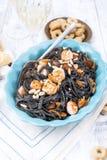 Italiensk pasta är svart med musslor och räkor Parmesan, skaldjur och vin för matställe Ljus disk och vit bakgrund arkivbild