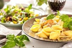 Italiensk pasta i en krämig sås med sallad på en platta, närbild royaltyfri fotografi