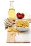Italiensk pasta, makaronivingpennor med körsbärsröda tomater och olivolja i en glasflaska Royaltyfria Bilder