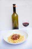 Italiensk pasta med en flaska av vin Arkivfoto
