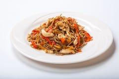 Italiensk pasta med höna och peppar i en vit platta på en ljus bakgrund Royaltyfri Foto