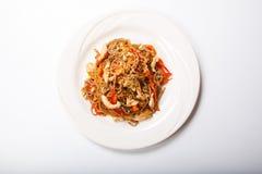 Italiensk pasta med höna och peppar i en vit platta på en ljus bakgrund Arkivfoto