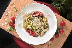 Italiensk pasta med parmesanost och körsbärsröda tomater arkivbild