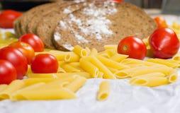 Italiensk pasta med tomater och skivor av bröd med mjöl på en vitbok arkivfoton