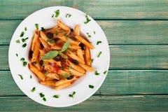 Italiensk pasta med tomater på den vita plattan Royaltyfri Bild