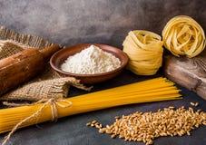 Italiensk pasta, spagetti, fettuccine, vete, kavel, mj?l p? en texturerad bakgrund lantlig livstid style fortfarande element royaltyfria bilder