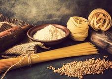 Italiensk pasta, spagetti, fettuccine, vete, kavel, mj?l p? en texturerad bakgrund lantlig livstid style fortfarande Tappning royaltyfri bild