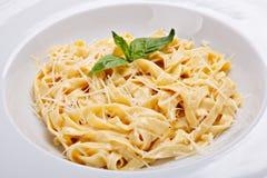 Italiensk pastaplatta för närbild med grated parmesan och bas Arkivbild