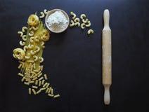 Italiensk pastaspagetti, tagliatelle, fusilli, cavatappi på svart bakgrund Pasta i formen av ett halvmånformig arkivbild