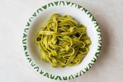 Italiensk pastaspenatFettuccine tjänade som med klart att äta för platta/tagliatelle arkivbild
