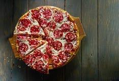 Italiensk peperonipizza med salami på bästa sikt för mörk träbakgrund Arkivbild