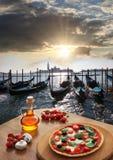 Italiensk pizza i Venedig mot kanalen, Italien Arkivfoto