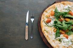 Italiensk pizza med burrataost, tomater och basilika på svartstenbakgrund med kniv- och gaffelkopieringsutrymme Top besk?dar fotografering för bildbyråer