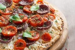Italiensk pizza med salami och tomater, närbild Royaltyfri Bild